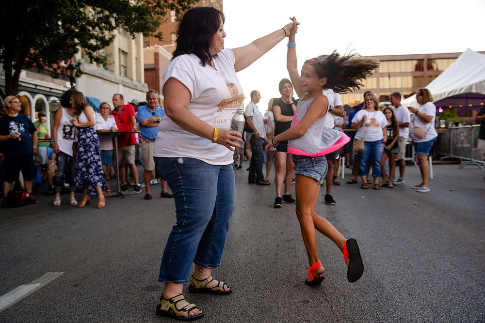 "Dee Rentmeister twirls her niece Sophie Rentmeister around as they listen to Amy Benton during the ""Amaranth Apple"" Music & Food Fest downtown Friday, July 14, 2017. The festival continues Saturday when gates open at 3 p.m.. [Ted Schurter/The State Journal-Register]"