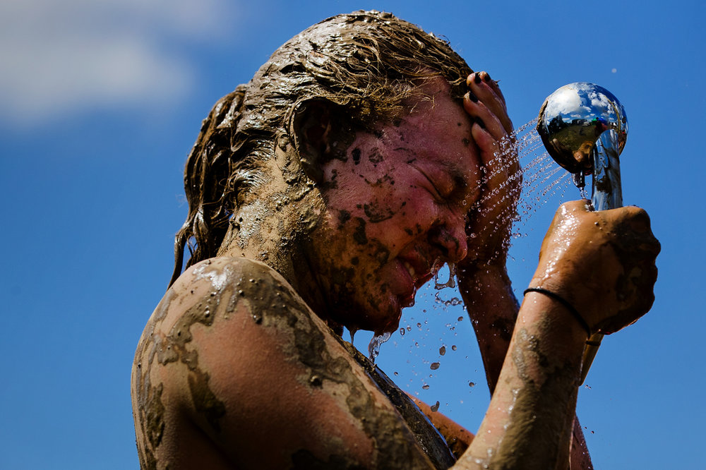 Rose Milcic rinses the mud off her face after competing in the Big Dawg Dare in Litchfield Saturday, July 15, 2017 [Ted Schurter/The State Journal-Register]