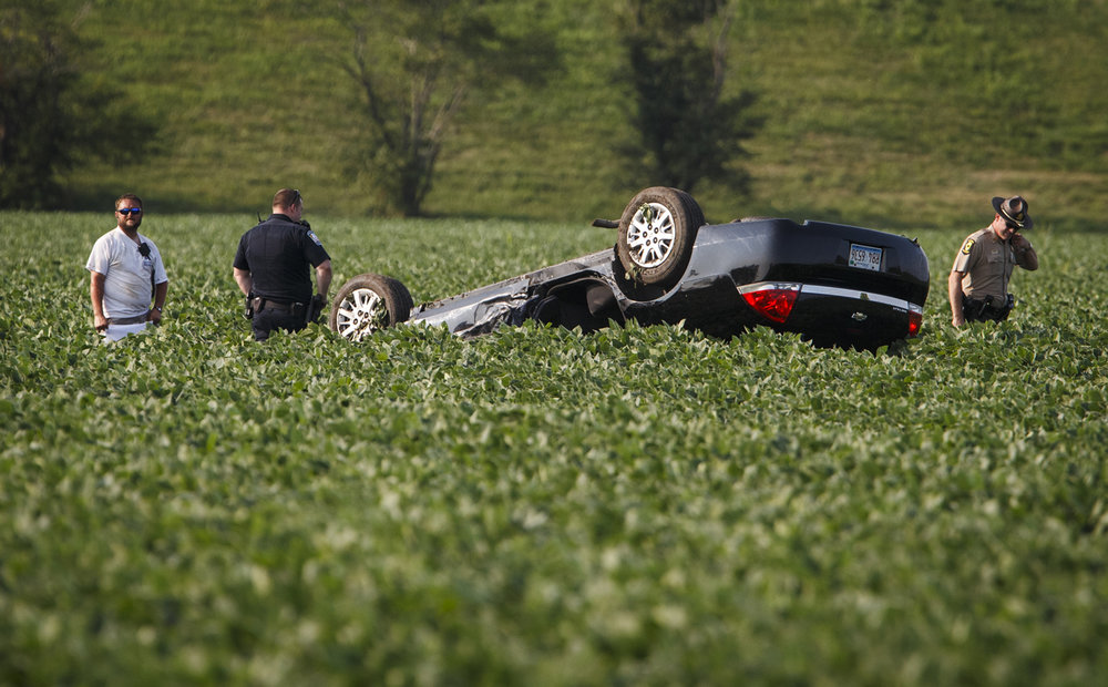 Illinois State Police and fellow law enforcement officers work the scene of a single vehicle that came to rest in a soybean field after a rollover accident just south of the New City Road overpass in the northbound lanes of I-55, Monday, July 17, 2017, south of Springfield, Ill. Scanner traffic indicated that the driver of the vehicle was associated with law enforcement. [Justin L. Fowler/The State Journal-Register]