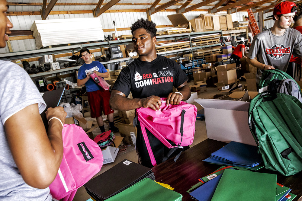 Springfield High School junior Caleb Small, 16, joins his fellow athletes from the SHS basketball and football teams as they volunteer their time to pack backpacks for kids from kindergarten to 8th with school supplies for the First Day Fund at Michael von Behren Builders, Wednesday, July 19, 2017, in Springfield, Ill. [Justin L. Fowler/The State Journal-Register]