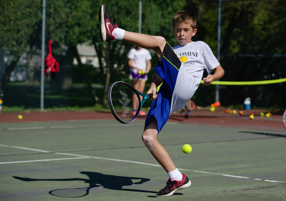 Aidan Petrone lifts his leg to try and hit a backhand shot during the Giacomini Tennis Academy at Southern View Community Park Monday, July 24, 2017. The academy will be under new leadership after Dominic and Patricia Giacomini retire after nearly a decade and a half of hosting the event. [Ted Schurter/The State Journal-Register]