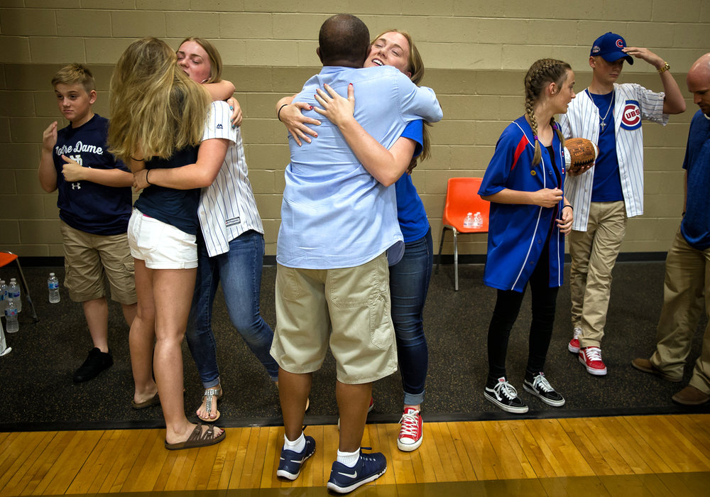 Madeline Rockford, center, gets a hug from Southeast boys basketball head coach Lawrence Thomas, as she and her siblings Connor, left, Abigail, Elizabeth and Andrew, right, are greeted during a memorial for their father, Steve Rockford, inside Jim Belz Gymnasium at the Sacred Heart-Griffin West Campus, Tuesday, July 25, 2017, in Springfield, Ill. Steve Rockford, the former Southeast High School wrestling coach who has been battling Lou Gehrig's disease since May 2012, passed away on July, 22, 2017. [Justin L. Fowler/The State Journal-Register]