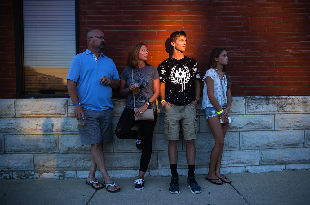 A pocket of reflected sunlight illuminates Jack Rogers as he listens to music with his parents Darin and Janelle and sister Ella at the Downhome Music Festival in downtown Springfield Friday, July 28, 2017. The festival features original local bands, food vendors and 100 different craft beers. [Ted Schurter/The State Journal-Register]