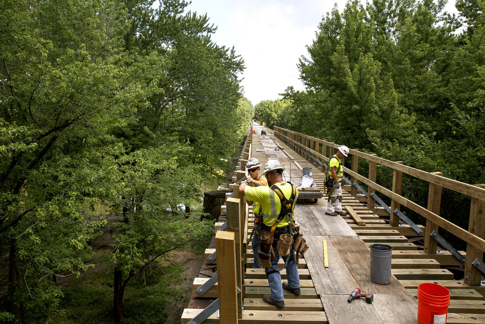 Jason Coats, Patrick Colgan and Mark Henson, carpenters for Halverson Construction Co.,  install side railings on the bridge that carries the Sangamon Valley Trail bike path over the Sangamon River Monday, July 24, 2017. The 900-foot long bridge, which is 100 feet above the river and offers spectacular views of the area, is the centerpiece feature of the trail extension now under construction. Remaining work includes finishing the bridge deck, installing fences along the path and paving the section north of the bridge to the trail end near the Sangamon-Menard County line. The trail is expected to open this fall. [Rich Saal/The State Journal-Register]