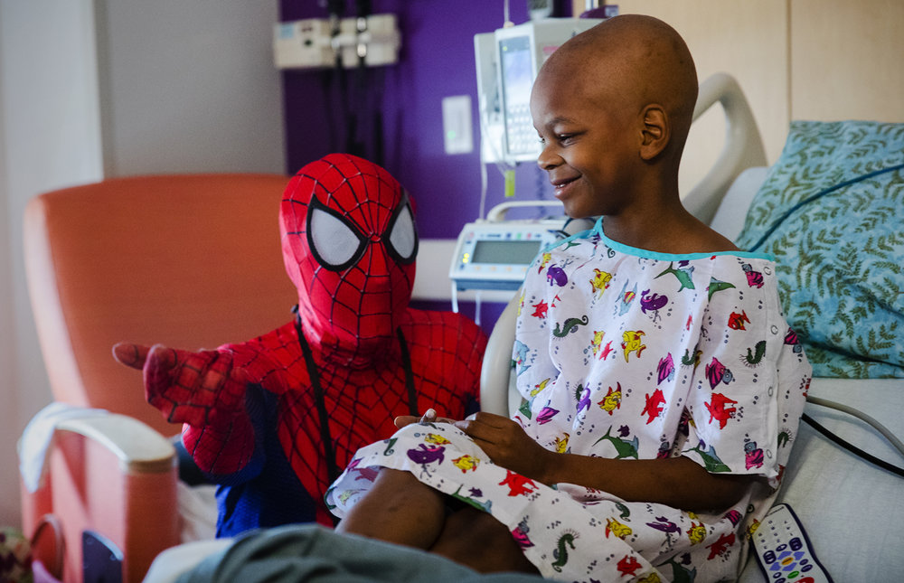 Seven-year-old Omeir Gales smiles as Spiderman, portrayed by Jonathan Warren with the group Superheroes Saving Smiles, demonstrates how he shoots webs during a visit to HSHS St. John's Children's Hospital Monday, July 31, 2017. Gales, who has cancer, said his bedroom is covered with Spiderman, his favorite superhero. [Ted Schurter/The State Journal-Register]
