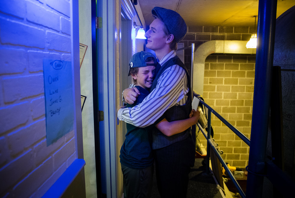 "Jacob Giacomini hugs Levi Ehrmantraut as they get into costume for the final production of ""Newsies"" at the Legacy Theatre Sunday, July 30, 2017. The Legacy is one of only 12 theaters in the country to be licensed to perform ""Newsies"" and, due to its popularity, added three shows to the original 13-show run. [Ted Schurter/The State Journal-Register]"