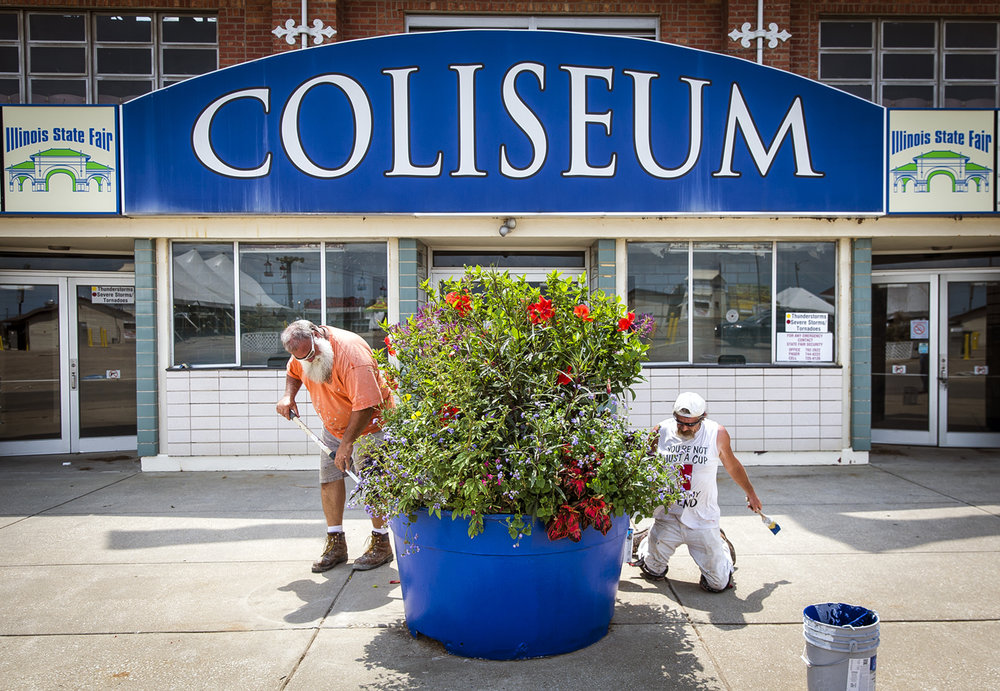 "Dave ""Santa"" Harris, left, and Tony Roberts, right, both journeyman painters with Painters Local 90, put a fresh coat of paint on one of the planters outside of the Coliseum as preparations are under ay for the Illinois State Fair at the Illinois State Fairgrounds, Thursday, Aug. 3, 2017, in Springfield, Ill. The planters and trash cans around the fairgrounds are being repainted either in red, white, or blue. Learn more about this year's fair by listening to the newest episode of the SJ-R Podcast, which features an interview with state fair manager Kevin Gordon. Visit bit.ly/ISFpodcast to listen now. [Justin L. Fowler/The State Journal-Register]"