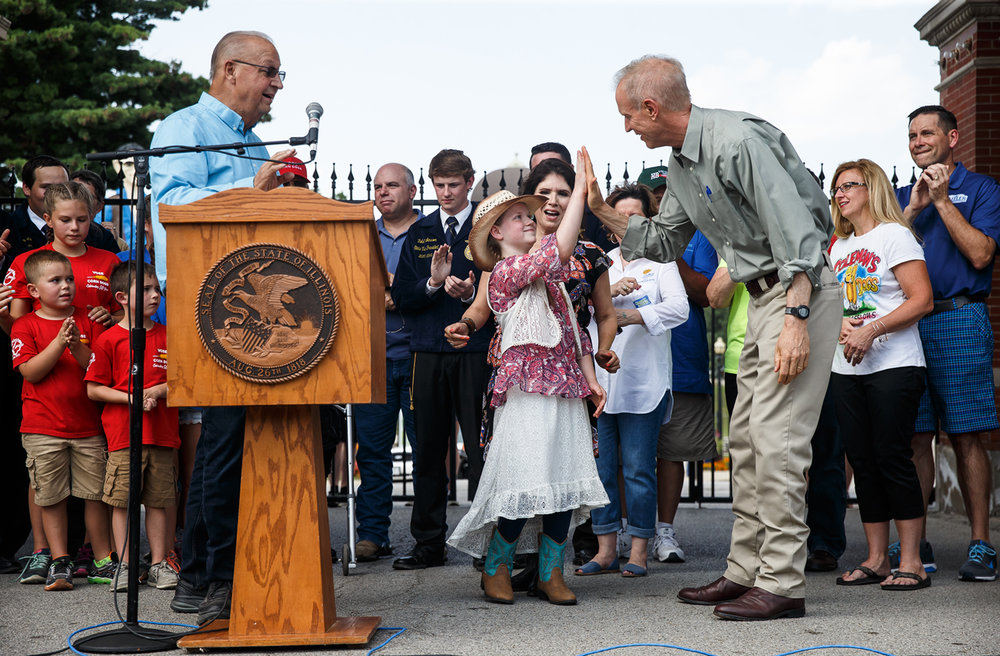 Illinois Governor Bruce Rauner gives Moriah Williams, 10, of Delavan, Ill., a high five after she sang the National Anthem during the ribbon cutting to officially open the 2017 Illinois State Fair at the Main Gate, Thursday, Aug. 10, 2017, in Springfield, Ill. [Justin L. Fowler/The State Journal-Register]