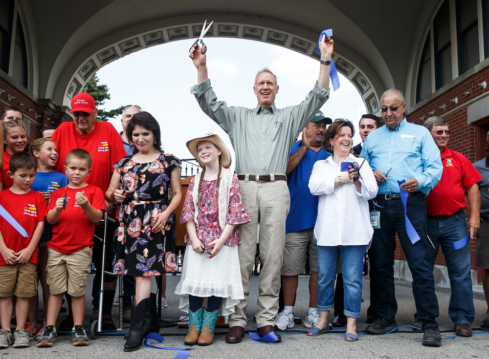 Illinois Governor Bruce Rauner celebrates the official opening of the 2017 Illinois State Fair along with Lt. Governor Evelyn Sanguinetti, Illinois Department of Agriculture Director Raymond Poe and members of Vose, Cullers and Coleman families, who have sold food at the fair for a combined 176 years, after the ribbon cutting at the Main Gate, Thursday, Aug. 10, 2017, in Springfield, Ill. [Justin L. Fowler/The State Journal-Register]