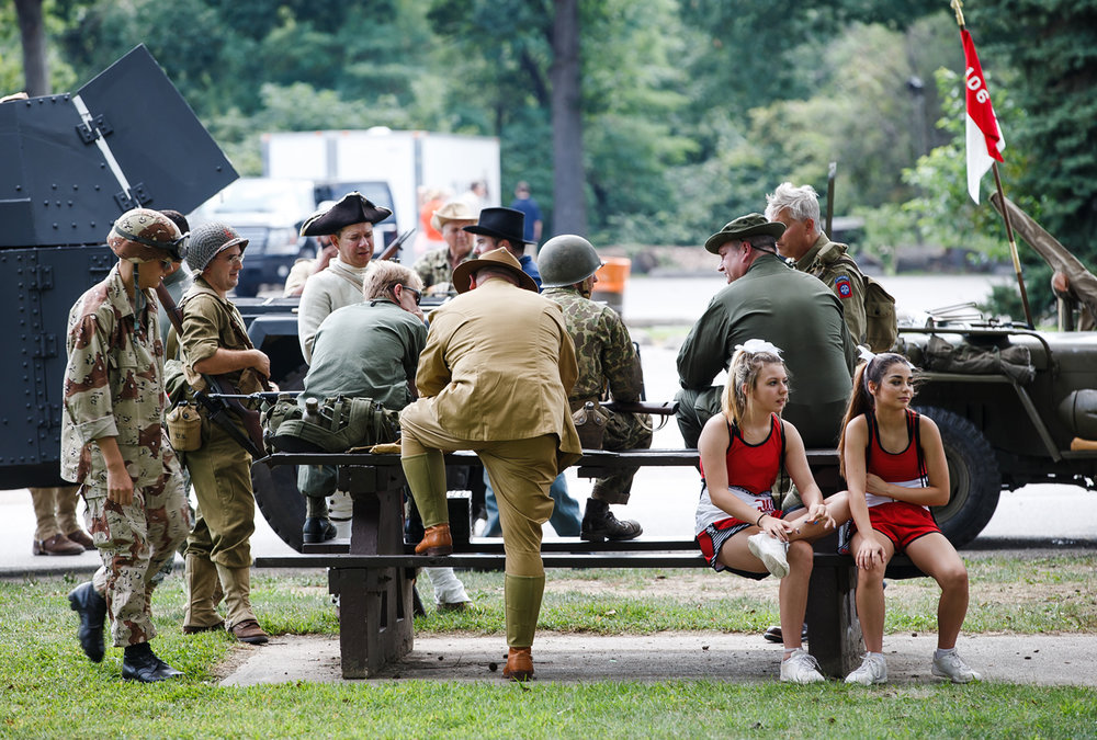 Military re-enactors share a park bench from members of the Springfield High School cheerleaders as they wait to get in line for the new parade route inside Lincoln park for the Illinois State Fair Twilight Parade, Thursday, Aug. 10, 2017, in Springfield, Ill. [Justin L. Fowler/The State Journal-Register]
