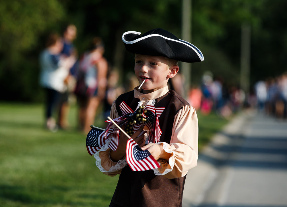 Caleb Cohen, 7, hands out American Flags with the Sons of the American Revolution inside Lincoln Park along the new route of the Illinois State Fair Twilight Parade, Thursday, Aug. 10, 2017, in Springfield, Ill. [Justin L. Fowler/The State Journal-Register]
