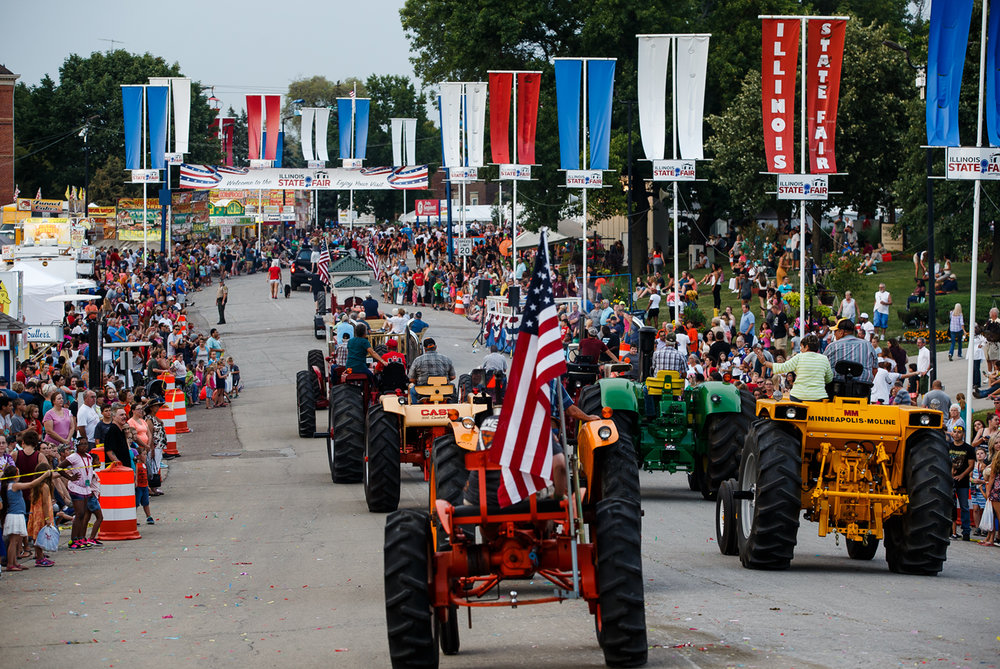 Antique tractors make their way down Main Street during Illinois State Fair Twilight Parade at the Lincoln Park, Thursday, Aug. 10, 2017, in Springfield, Ill. [Justin L. Fowler/The State Journal-Register]