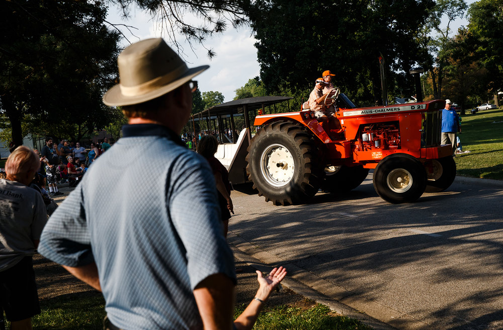 An antique tractor meant to carry the families of the Grand Marshals has to turn around inside Lincoln Park to get into the line prior to the start of the Illinois State Fair Twilight Parade, Thursday, Aug. 10, 2017, in Springfield, Ill. [Justin L. Fowler/The State Journal-Register]