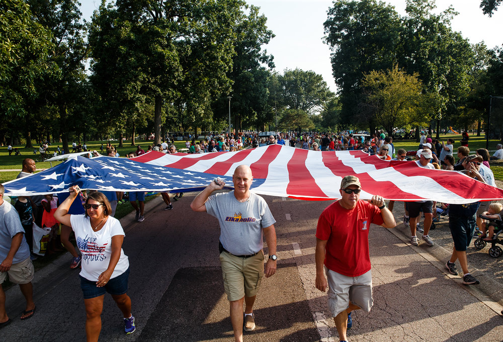 Members of the Illinois Elks Lodge 158 carry the large American Flag through Lincoln Park along the new route of the Illinois State Fair Twilight Parade, Aug. 10, 2017, in Springfield, Ill. [Justin L. Fowler/The State Journal-Register]
