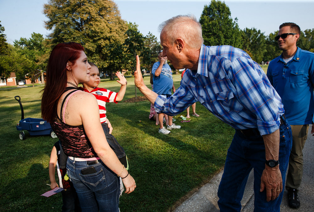 Tyesin Gross, 2, gets a high five from Illinois Governor Bruce Rauner, right, along with his mother Jerika Graham, along the new Illinois State Fair Twilight Parade route in Lincoln Park, Thursday, Aug. 10, 2017, in Springfield, Ill. [Justin L. Fowler/The State Journal-Register]