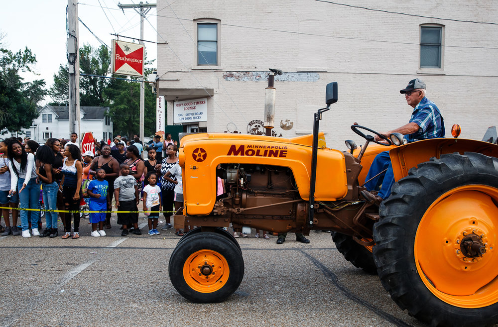 Antique tractors make their way to the Main Gate from Sangamon Avenue on the new route of the Illinois State Fair Twilight Parade, Thursday, Aug. 10, 2017, in Springfield, Ill. For years, the parade started at North Grand and headed north along Ninth Street and Peoria Road toward the fairgrounds. This year, it started at Lincoln Park and headed east along Sangamon Avenue to the fairgrounds. [Justin L. Fowler/The State Journal-Register]