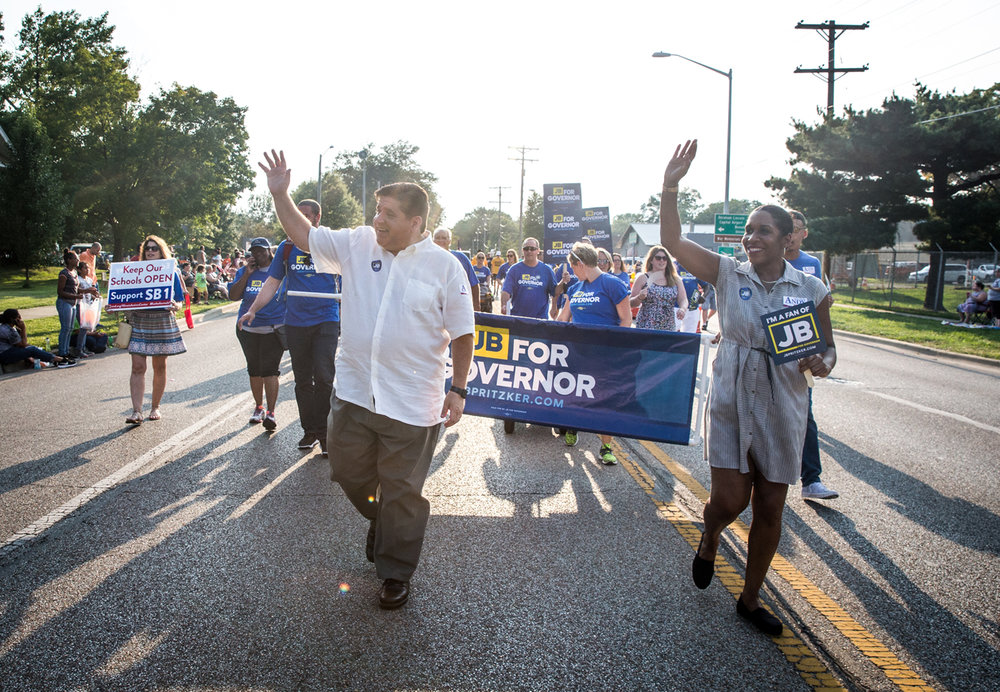 Democratic governor candidate J.B. Pritzker, center, marches with running mate, Rep. Juliana Stratton, right, along Sangamon Avenue during Illinois State Fair Twilight Parade, Thursday, Aug. 10, 2017, in Springfield, Ill. [Justin L. Fowler/The State Journal-Register]