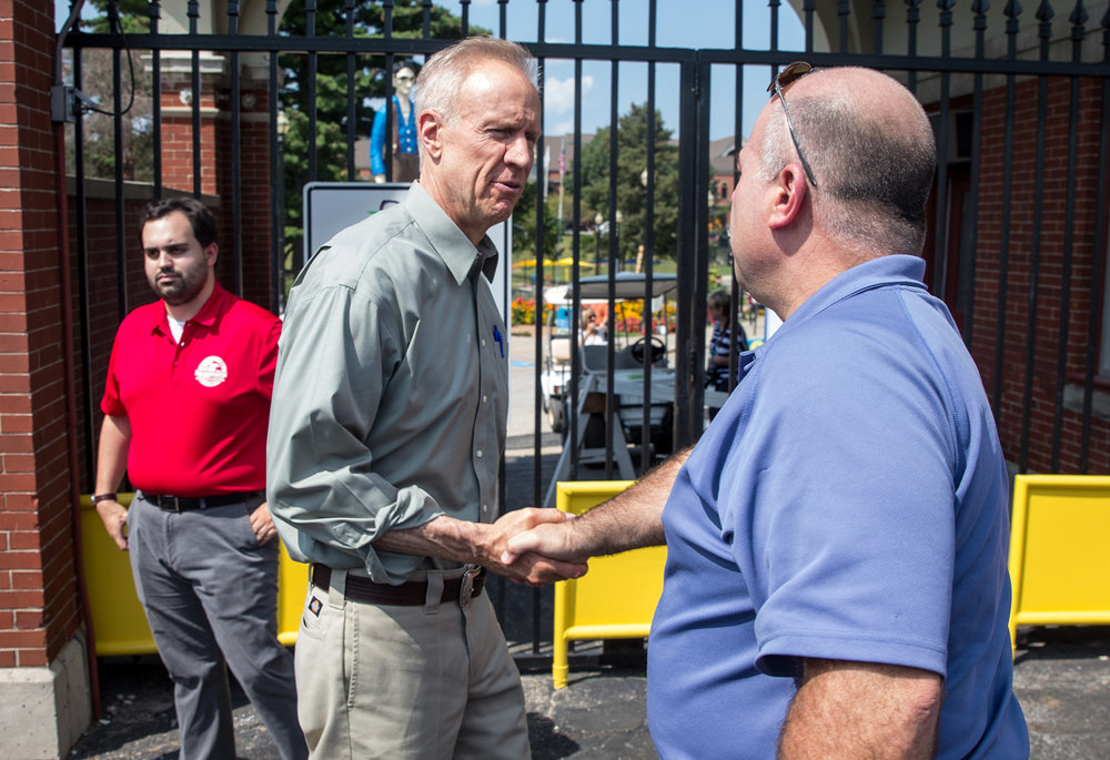 Illinois Governor Bruce Rauner shakes hands with Illinois State Sen. Sam McCann, R-Plainview, prior to the ribbon cutting to officially open the 2017 Illinois State Fair at the Main Gate, Thursday, Aug. 10, 2017, in Springfield, Ill. [Justin L. Fowler/The State Journal-Register]
