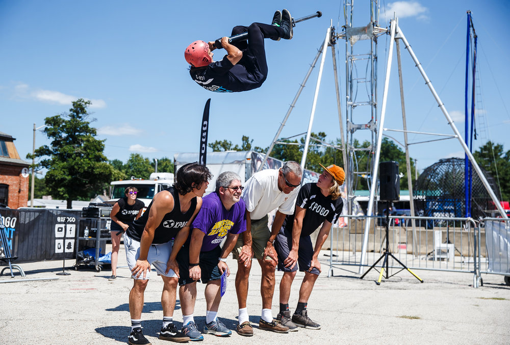 Dalton Smith, 20, of Nashville, Tenn., performs a front flip over his team members and volunteers from the audience while performing with the Xpogo Stunt Team in the Thrillville area near Gate 2 at the Illinois State Fairgrounds, Saturday, Aug. 12, 2017, in Springfield, Ill. [Justin L. Fowler/The State Journal-Register]