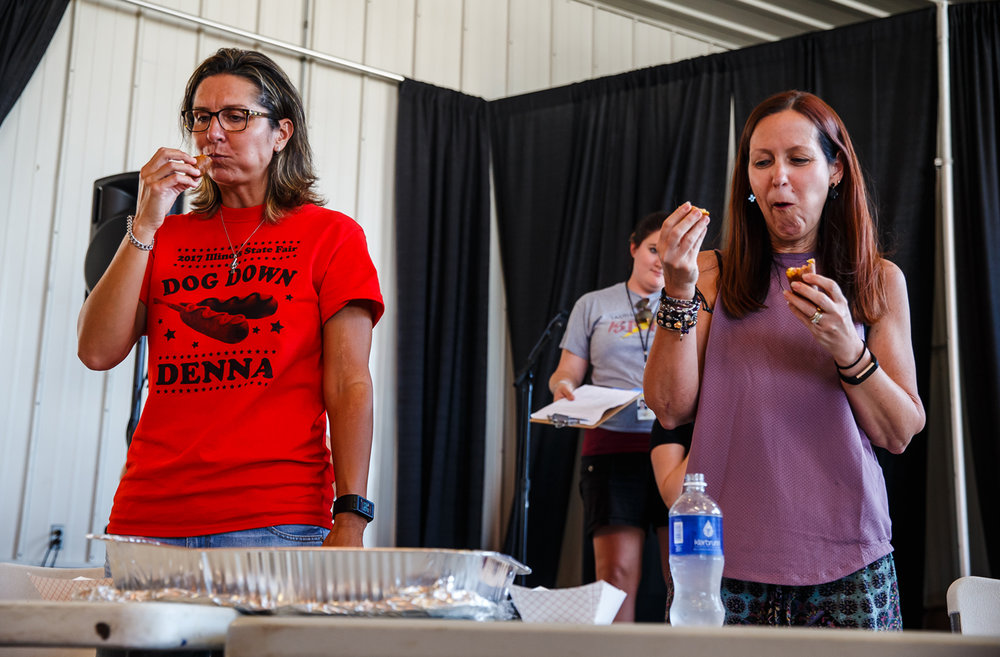 Denna Mooney, left, and Holly Dahlquist, right, do their best to stuff down the corn dogs during the 2017 Illinois State Fair Corn Dog Eating Contest at The Shed at the Illinois State Fairgrounds, Saturday, Aug. 12, 2017, in Springfield, Ill. [Justin L. Fowler/The State Journal-Register]
