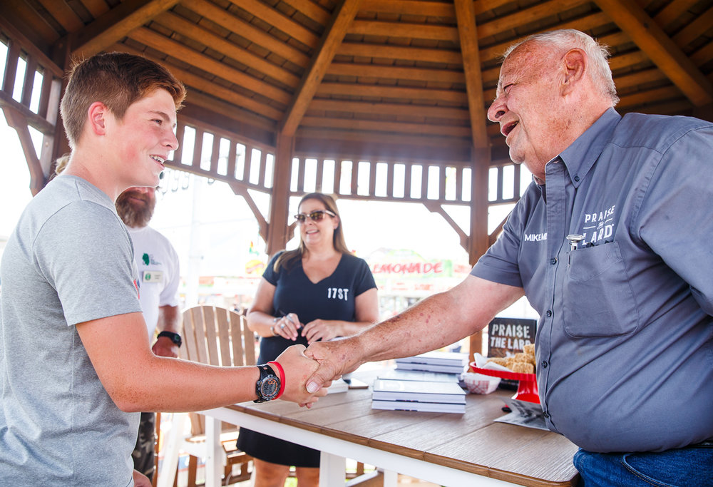 "Mike Mills, right, of 17th Street BBQ shakes hands with Owen Espel, 14, during a book signing for ""Praise The Lard,"" a new book written in tandem with his daughter Amy Mills, center, at the the 17th Street BBQ stand at the Illinois State Fairgrounds, Sunday, Aug. 13, 2017, in Springfield, Ill. [Justin L. Fowler/The State Journal-Register]"