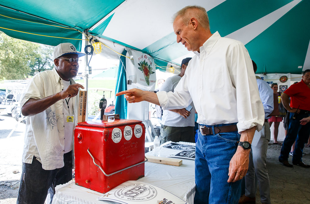 Illinois Governor Bruce Rauner asks for a sample from Alfred Brown Sr. with the Sketchbook Brewing Company out of Evanston, Ill., at the Illinois Bicentennial Craft Beer Competition on the Illinois State Fairgrounds, Sunday, Aug. 13, 2017, in Springfield, Ill. [Justin L. Fowler/The State Journal-Register]