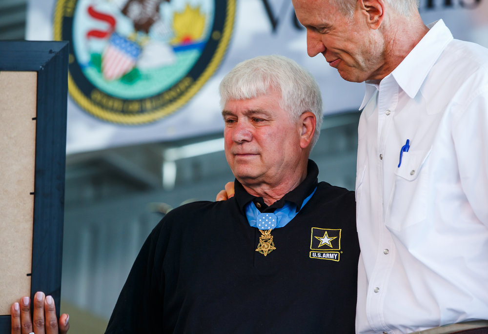 Medal of Honor recipient Specialist Five James C. McCloughan, becomes emotional as he gets a hug from Illinois Governor Bruce Rauner as he is honored during the Veterans and Gold Star Family Day program on the Lincoln Stage at the Illinois State Fairgrounds, Sunday, Aug. 13, 2017, in Springfield, Ill. [Justin L. Fowler/The State Journal-Register]