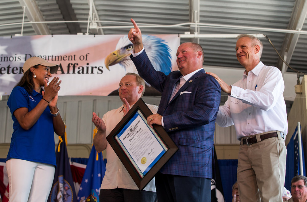 PJ Staab, center, acknowledges a person in the crowd after Staab Funeral Home is honored as the Illinois Veterans Business of the Year by Illinois Governor Bruce Rauner and Illinois Sept. of Veterans' Affairs director Erica Jeffries, left, during the Veterans and Gold Star Family Day program on the Lincoln Stage at the Illinois State Fairgrounds, Sunday, Aug. 13, 2017, in Springfield, Ill. [Justin L. Fowler/The State Journal-Register]