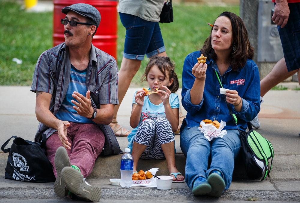 Ivy Corman, 5, navigates a fired cheese curd while enjoying a break along with ice cream with her father Jeff Corman, left, and Erin Goldstein, right, during the Illinois State Fair at the Illinois State Fairgrounds, Sunday, Aug. 13, 2017, in Springfield, Ill. [Justin L. Fowler/The State Journal-Register]