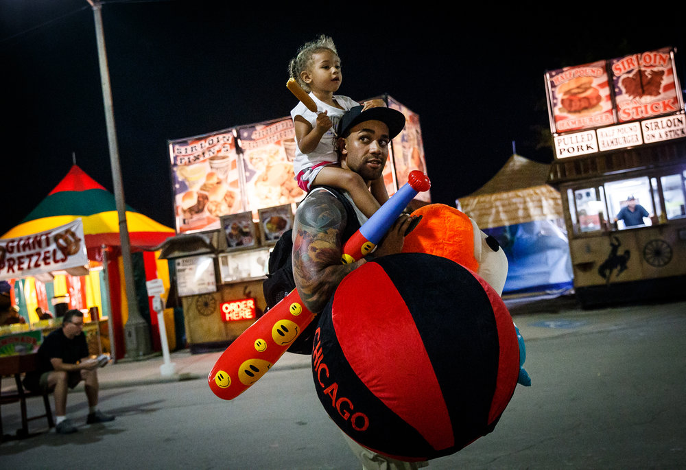 Simmi Caves, 2, hitches a ride on the shoulders of her farther Donnie Caves as he carries their winnings from the carnival games during the Illinois State Fair at the Illinois State Fairgrounds, Sunday, Aug. 13, 2017, in Springfield, Ill. [Justin L. Fowler/The State Journal-Register]