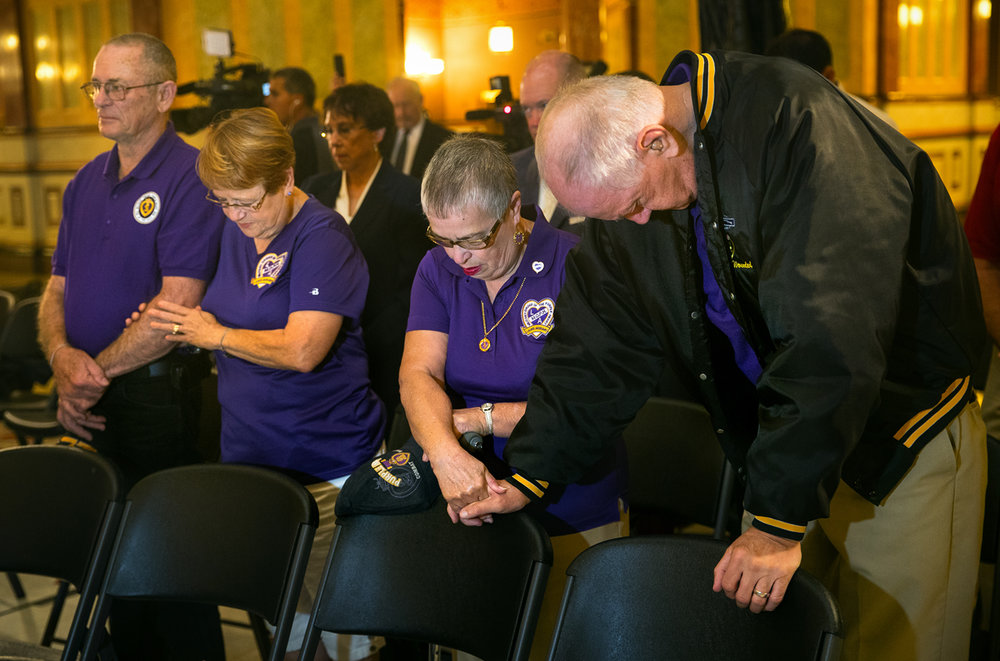 Thomas and Pat Halberstadt, left and Joyce and Larry Taylor listen to an opening prayer during a Purple Heart Day ceremony at the Illinois State Capitol Rotunda Monday, Aug. 7, 2017. The ceremony honored Purple Heart recipients, including Thomas and Taylor. In honor and tribute to all Purple Heart Recipients, the Capitol Grounds in Springfield and the Daley Plaza Fountain will be lit in purple the night of August 7, 2017. [Ted Schurter/The State Journal-Register]
