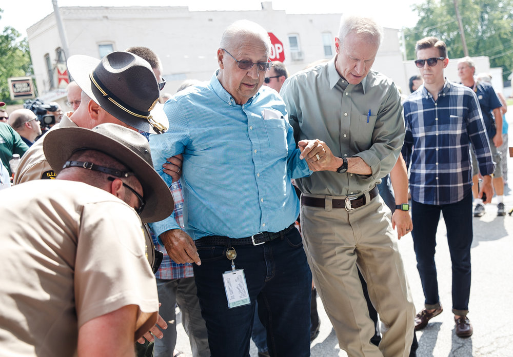 Illinois Governor Bruce Rauner helps Illinois Dept. of Agriculture Director Raymond Poe to his feet after he fell during the ribbon cutting for the 2017 Illinois State Fair at the Main Gate, Thursday, Aug. 10, 2017, in Springfield, Ill. [Justin L. Fowler/The State Journal-Register]