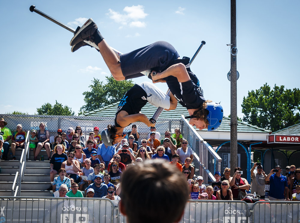 Nic Patino, 19, of New Hope, Penn., left, and Flynn Nyman, 14, of Corvallis, Oregon, perform flips simultaneously as they perform with the Xpogo Stunt Team in the Thrillville area near Gate 2 at the Illinois State Fairgrounds, Saturday, Aug. 12, 2017, in Springfield, Ill. [Justin L. Fowler/The State Journal-Register]