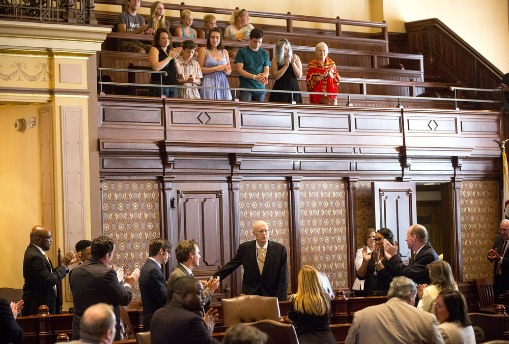 Senate colleagues warmly welcome Sen. Bill Haine, D-Alton, back to the Senate Sunday, Aug. 13, 2017. Haine has been undergoing treatment for cancer since February but was at the Capitol to vote to override Gov. Bruce Rauner's amendatory veto to the school funding reform bill, SB1. Haine's wife, Anna, top right, and several of their grandchildren were in the gallery. [Rich Saal/The State Journal-Register]