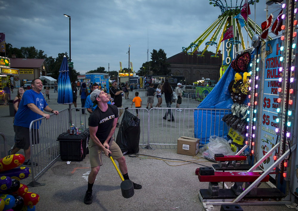 Sean Orlando watches his attempt to ring the bell fall short during a friendly contest with his friend Joshua Cole, left, at the Hi Striker in the carnival at the Illinois State Fair Monday, Aug. 14, 2017. [Rich Saal/The State Journal-Register]