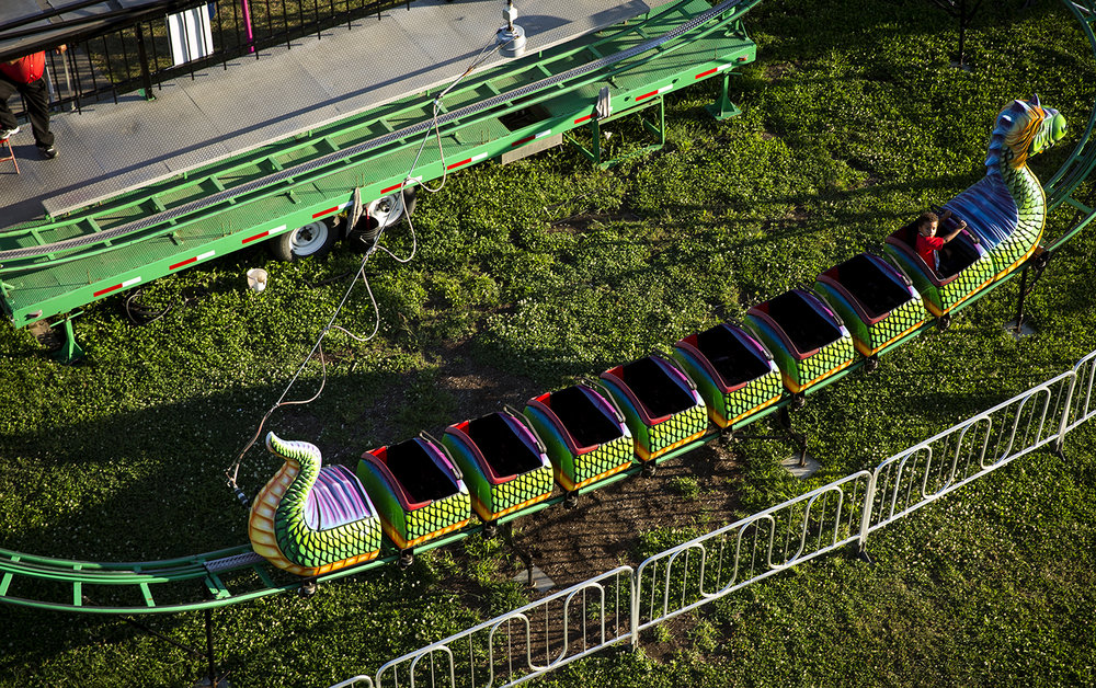 The dragon roller coaster in Adventure Village, carrying a single passenger, circles its track Thursday, Aug. 17, 2017 at the Illinois State Fair. [Rich Saal/The State Journal-Register]
