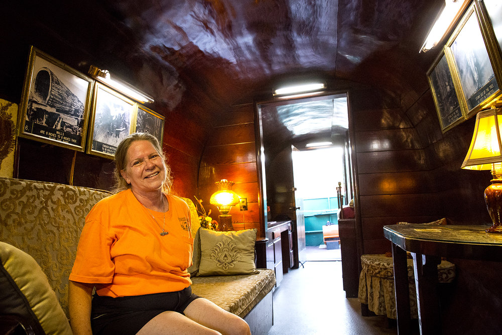 "Jamie Allen, the ""Log Lady,"" sits inside a hollowed redwood log built in 1939 by her grandfather, Jim Allen, at the Illinois State Fair Thursday, Aug. 17, 2017. Mr. Allen was a logger during the Depression who bartered for the 33-foot long section and then spent four months carving out the inside and another 1 1/2 years making it into his home. It was Jamie's father who had the idea of touring the tree at fairs and festivals, thinking it was unique enough to attract visitors. The log house has been a fixture on and off at the State Fair since the 1960s and Jamie, who is now the caretaker, has brought it to Springfield the past five years. ""It's expensive,"" Allen says of taking the log on the road and doesn't know how much longer she'll keep it up. She admits that if the right buyer were to come along, it's for sale. [Rich Saal/The State Journal-Register]"