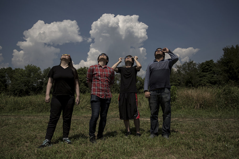 Eugene Cho, left, Suyup Kim, Shotaro Ikeda and Surya Bakshi, University of Illinois students from Champaign, watch the eclipse as it nears totality Monday, Aug. 21, 2017 in Giant City State Park near Carbondale. As the moon blocks more of the sun, colors become muted and contrast diminishes. [Rich Saal/The State Journal-Register]