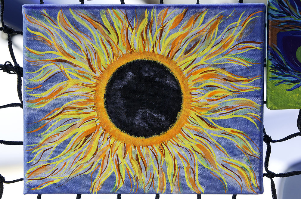 Only one glow-in-the-dark eclipse painting remains at Jennifer Kaiser's Jeniflower's Gallery tent at the Carbondale Eclipse Marketplace in downtown Carbondale Saturday, Aug. 19, 2017. Kaiser said she created six and sold five within hours of opening Saturday morning. [Ted Schurter/The State Journal-Register]