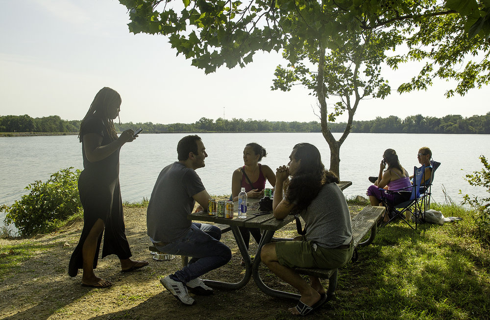 """Former college roomates Alex Marson, left, and Cassim Shepard, along with Shepard's wife Heather McGhee, left, and her sister Shannon McGhee visit on a tiny pennisula of land that stretches into the Carbondale Reservoir as they wait for the total solar eclipse Monday, Aug. 21, 2017.  Shepard said he's been waiting to view the eclipse since he saw a commercial for the Mitsubishi Eclipse as a nine-year-old that advertised the 2017 event. """"I thought the future would be here,"""" Shepard said, who also thought we'd be traveling in solar-powered vehicles to the moon. [Ted Schurter/The State Journal-Register]"""