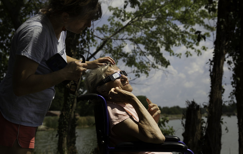 Maggie Pavlik strokes her mother Maria Salicka's hair as she gazes at the total solar eclipse at Evergreen Park in Carbondale, Ill., Monday, Aug. 21, 2017. [Ted Schurter/The State Journal-Register]