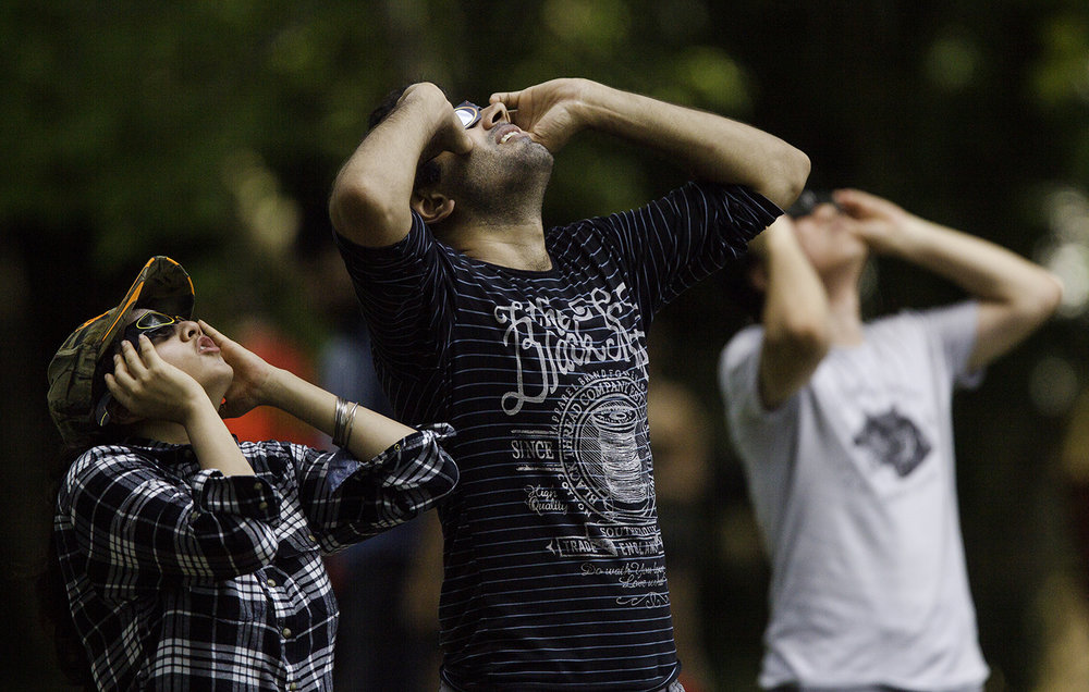People gaze at the solar eclipse at Evergreen Park in Carbondale, Ill., Monday, Aug. 21, 2017. [Ted Schurter/The State Journal-Register]