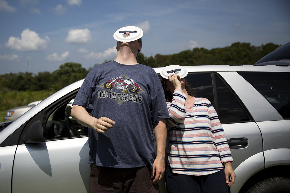 "Tammy and Paul Bronk use adapted eclipse glasses, to screen their faces from the sun, while viewing the early stages of the total solar eclipse from Giant City State Park near Carbondale Monday, Aug. 21, 2017. ""It went fast but yet it felt like time stood still. Twilight and still and perfect, it was so beautiful,"" Tammy Bronk said after totality had passed. [Rich Saal/The State Journal-Register]"