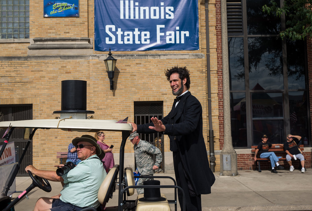 Randy Duncan, as Abraham Lincoln, takes a ride in the daily parade along Grandstand Avenue representing Looking For Lincoln during the 2017 Illinois State Fair at the Illinois State Fairgrounds, Thursday, Aug. 17, 2017, in Springfield, Ill. [Justin L. Fowler/The State Journal-Register]