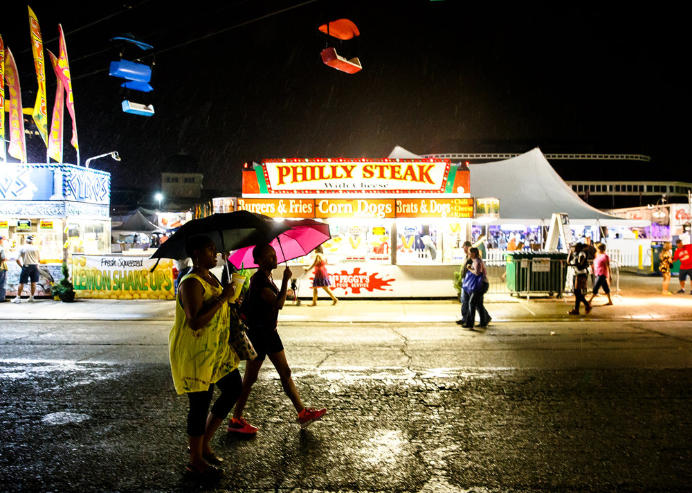 The umbrellas come out as a brief rain shower hits during the 2017 Illinois State Fair at the Illinois State Fairgrounds, Friday, Aug. 18, 2017, in Springfield, Ill. [Justin L. Fowler/The State Journal-Register]