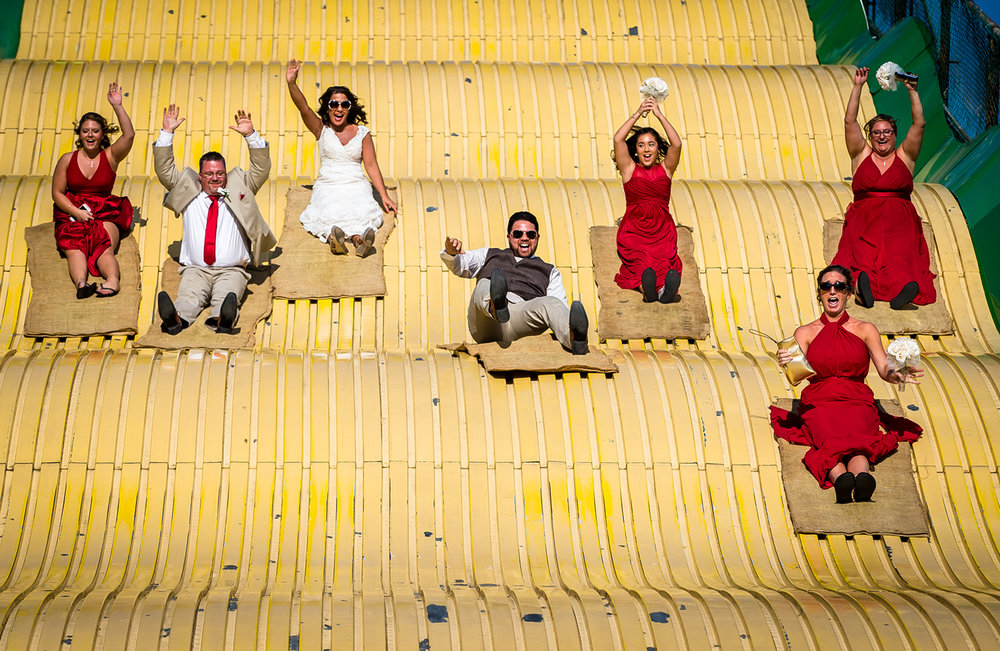 Jason Johnson, center, flies down the Giant Slide with his bride Erica Cusumano and members of the bridal party after stopping at the Illinois State Fair after their wedding, Saturday, Aug. 19, 2017, in Springfield, Ill. [Justin L. Fowler/The State Journal-Register]