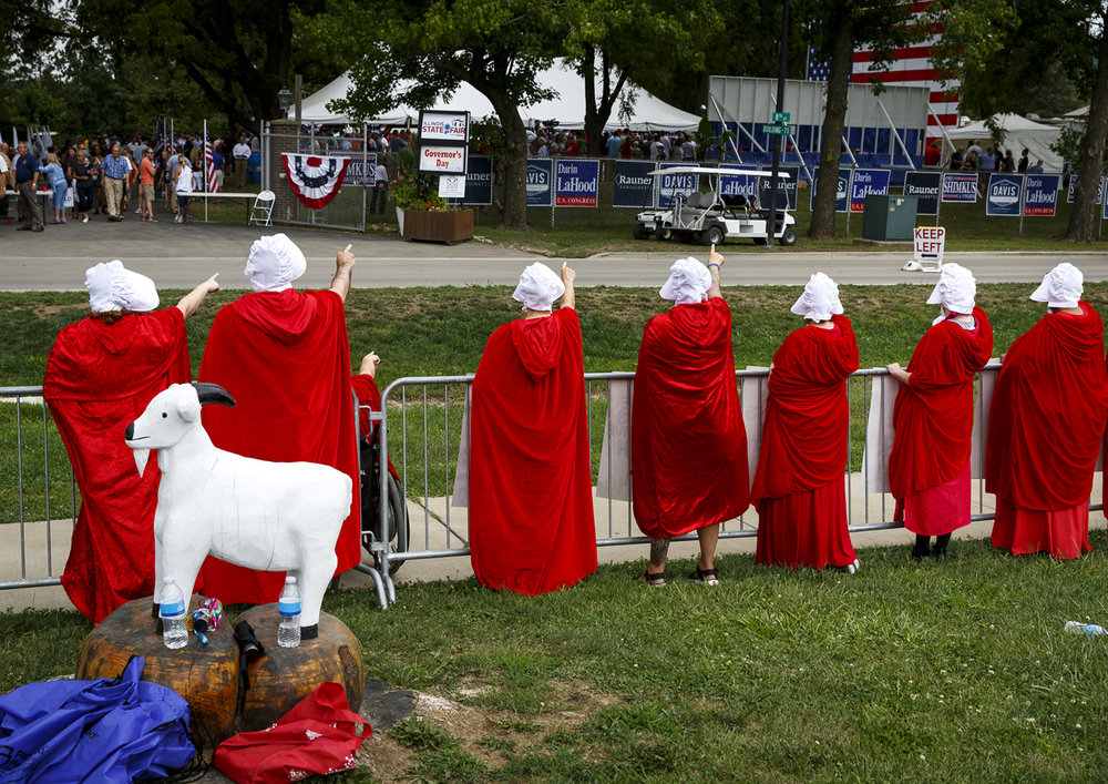 Womens rights activists dressed as characters from The Handmaid's Tale, stood across from the Governor's Day event at the Illinois State Fair Wednesday, Aug. 16, 2017. The group demonstrates against gender discrimination and supports reproductive and civil rights. [Rich Saal/The State Journal-Register]