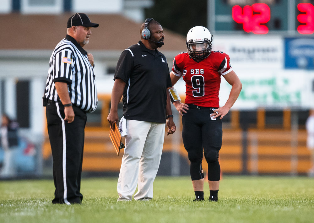 Springfield football head coach Roy Gully III talks with Springfield quarterback Lucas Rockford (9) on the sidelines as the Senators take on Normal U-High in the first quarter at Memorial Stadium, Friday, Aug. 25, 2017, in Springfield, Ill. [Justin L. Fowler/The State Journal-Register]