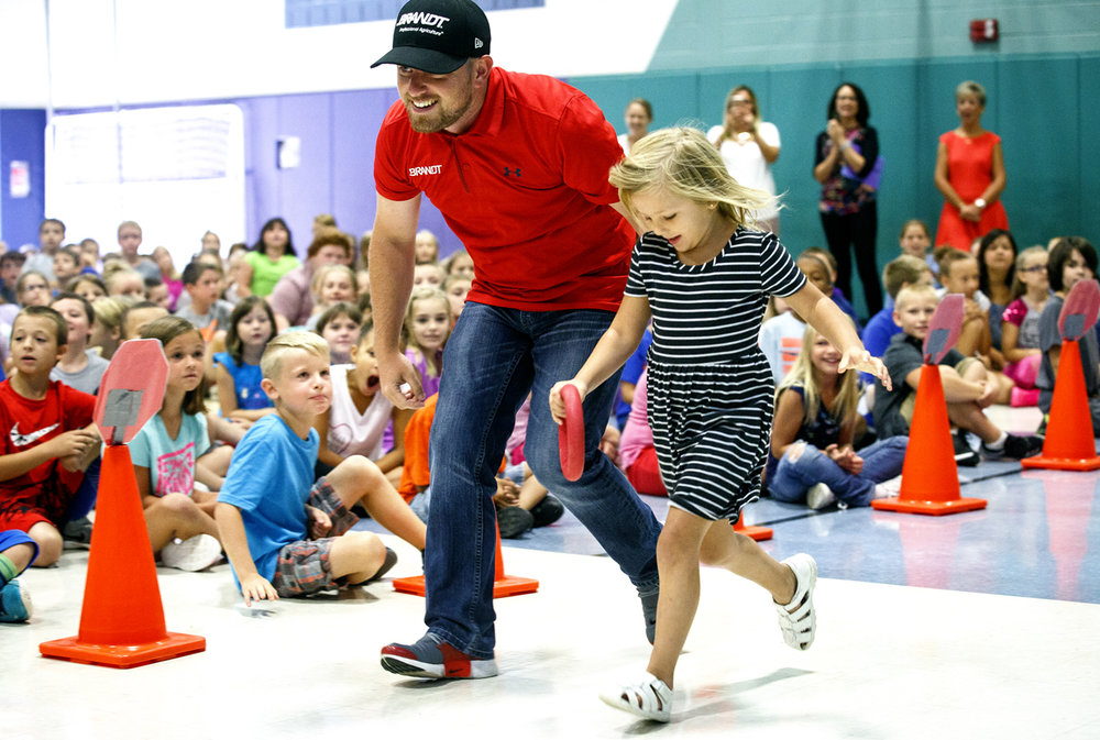Justin Allgaier, who races in the NASCAR Xfinity series for JR Motorsports, visited Riverton Elementary School where he was once a student and took part in racing games Tuesday, Aug. 15, 2017, running along side kindergartner Macee Cloud. [Rich Saal/The State Journal-Register]