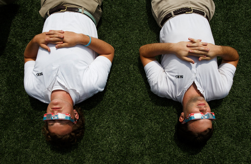 Sacred Heart-Griffin seniors Colin Mannion, left, and Cole Taylor, right, take in the total solar eclipse during a viewing on the football field for the students of SHG at the West Campus Sports Complex, Monday, Aug. 21, 2017, in Springfield, Ill. [Justin L. Fowler/The State Journal-Register]